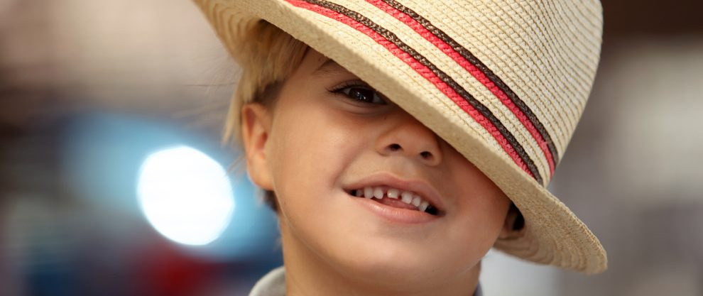 cute boy in fedora with crooked teeth