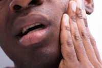 African-American man holding face from jaw pain